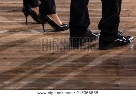 Male and female legs in black shoes and trousers on an old wooden parquet floor. Close up.