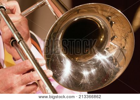The musician plays a jazz melody on a trombone. Close-up. For music news or for information on the musical theme.