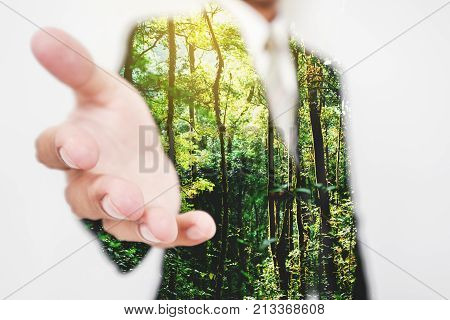 Double exposure, Businessman stretching hand to hand shake with Green trees in the forest. Eco friendly and sustainable business
