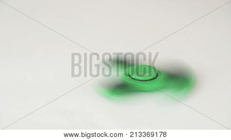 Green fidget spinner turns and stops on a white background