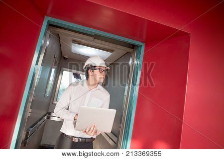 Young Asian engineer or architect holding laptop computer in elevator that surrounded by red wall. Civil engineering Architecture or building construction concepts