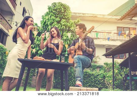 Group Of Young Asian People Happy While Enjoying Garden Party And Play Guitar On Garden Home