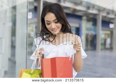Asian Women And Beautiful Girl Is Holding Shopping Bags Smiling While Doing Shopping In The Supermar