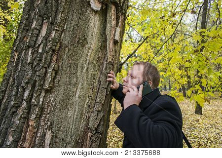 Handsome Young Man With A Smartphone On The Street Talking In The Park And Looking Up. Beautiful Aut