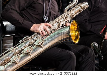 The saxophonist of the jazz collective sits on a chair and puts a baritone saxophone on his knees. For music news about jazz musicians or wind instruments.