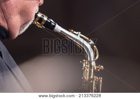 Elderly saxophonist with a second chin blowing into a saxophone.