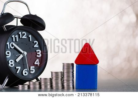 Model House Wood Form With Alarm Clock And Step Of Coins Stacks On Working Table, Time For Real Esta