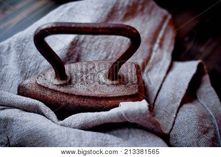 Old heavy cast-iron iron on a piece of burlap. Retro photo