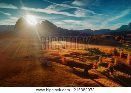 Aerial autumn sunrise scenery with yellow larches and small alpine building and Odle - Geisler mountain group on background. Alpe di Siusi (Seiser Alm) Dolomite Alps Italy.