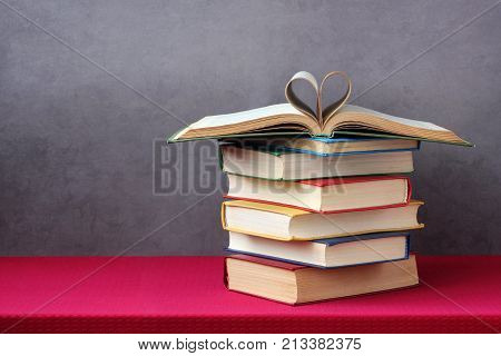 Love of books reading. Stack of books in the colored cover lay on the table. Open book with curled leaves in the shape of a heart. Library education. Empty space for Your text on the left.