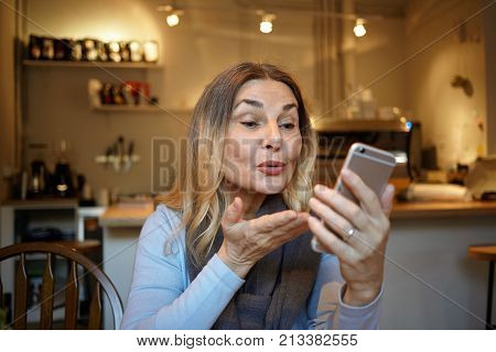 Picture of attractive mature woman holding mobile phone and blowing kiss while having video chat with her daughter sitting in kitchen. Beautiful senior female posing at home taking selfie