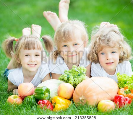 Group of happy children with fruits and vegetables lying on green grass in spring park. Healthy eating concept