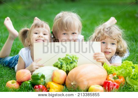 Group of happy children with fruits and vegetables outdoors in spring park