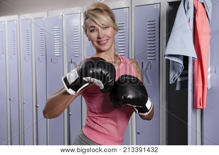 Senior blonde woman in gray pants and pink top, wearing boxing gloves stands on the background of the lockers in the locker-room in the gym.