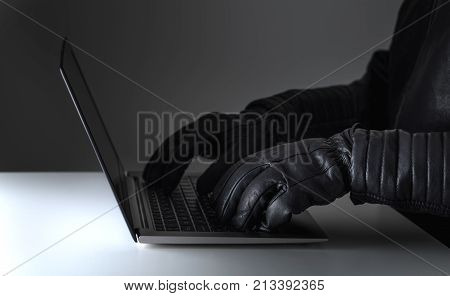 Cyber security threat attack and online crime concept. Hacker writing with laptop computer wearing leather gloves.