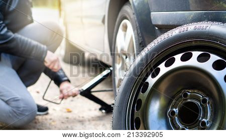 Driver changing spare tyre after accident. Broken and flat car wheel after crash. Man fixing problem with jack.