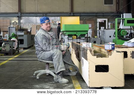 LIPETSK, RUSSIA - JUNE 15, 2017: Lipetsk Machine Tool Plant. The worker polishes the primer layer. Work on the preparation of the machine bed for subsequent painting.
