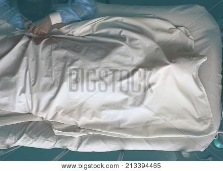 Young crying woman next to the deathbed of covered with bedsheet dead man.