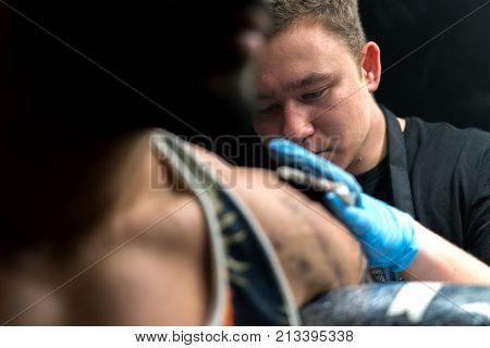 Cropped shot of tattooist doing tattoo on male shoulder. Tattoo master demonstrating the process of work.
