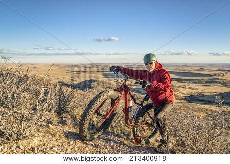 a senior male with a fat bike in Soapstone Prairie Natural Area in northern Colorado, late fall scenery