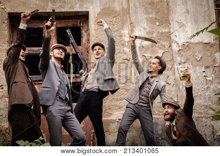 A group of gangsters with various dangerous weapons in their hands amidst an old abandoned building, they are celebrating something by raising their arms above their heads.