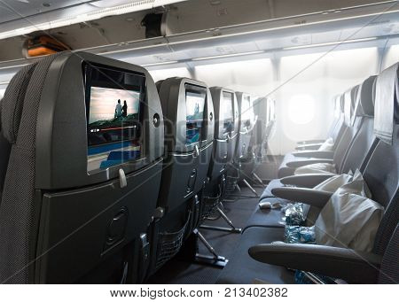 Seats waiting for passengers and take off in an airplane. Empty plane interior before flight and departure. Watching movie on an aircraft. Imaginary film playing on a video player in monitor.