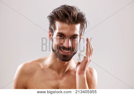 Young handsome man is ready to shave his beard. He is applying shaving foam.