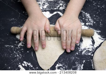 Little child preparing dough for backing. Kid's hands some flour wheat dough and rolling-pin on the black table. Children hands making the rye dough for backing bread. Small hands kneading dough
