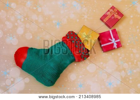 Green knitted christmas stocking with colorful gifts