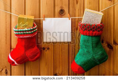 Christmas stockings and greeting card on wooden wall