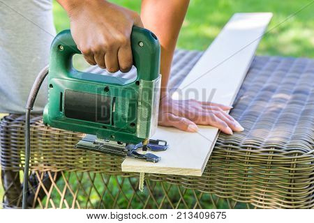 Woman sawing wooden plank with electric jig saw