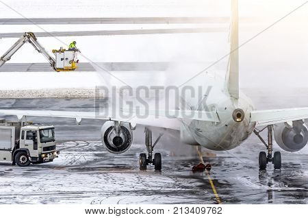 Ground Crew Provides De-icing. They Are Spraying The Aircraft, Which Prevents The Occurrence Of Fros