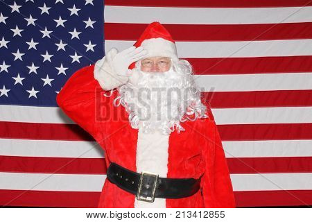 Santa Claus poses in front of an American Flag.  Santa Claus Salutes all our Veterans and Military while in front of an American Flag.