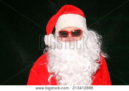 Santa Claus. Santa Claus poses for his photo to be taken in front of a green AstroTurf background.