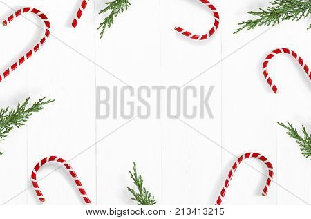 Christmas styled stock photo. White wooden background with candy cane decorations, evergreen juniperus branches and empty space, top view. Festive composition.