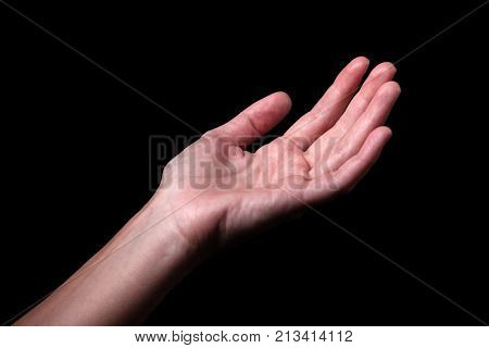Female hand reaching with palms up. Concept for begging, asking, needing, salvation, rescue, friendship, guidance, help, helping. Black background.