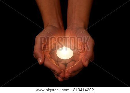 Hands holding and protecting lit or burning candle candlelight on darkness. Black background. Concept for prayer, praying, hope, vigil, night watch