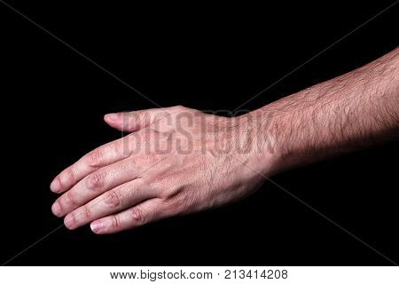 Male hand reaching or pointing down. Concept for salvation, rescue, friendship, guidance, help, helping. Black background.
