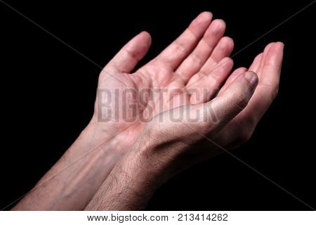 Male hands praying with palms up arms outstretched. Black background. Close up of man hand. Concept for prayer, faith, religion, religious, worship