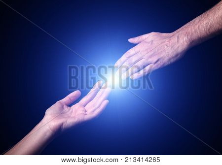 Reaching and touching hands. Bright light star flare with touching fingertips. Concept for salvation, rescue, friendship, guidance. Black background.