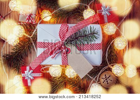 Christmas gift box on wooden background with Fir branches jingle bell small presents and Christmas light. Xmas and Happy New Year composition. Top view.