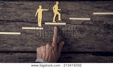 Business teamwork concept with the hand of businessman supporting paper cut outs of a man climbing the steps in vintage effect toned image.