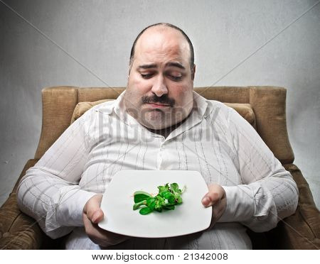 Sad fat man looking at a dish with some salad