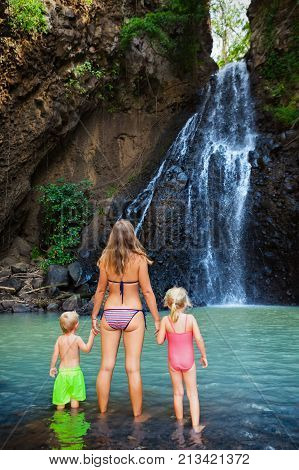 Mother with kids swim in water pool under waterfall in jungle canyon. Travel adventure hiking activity with child. Healthy lifestyle on family summer vacation and weekend recreational walking tour.