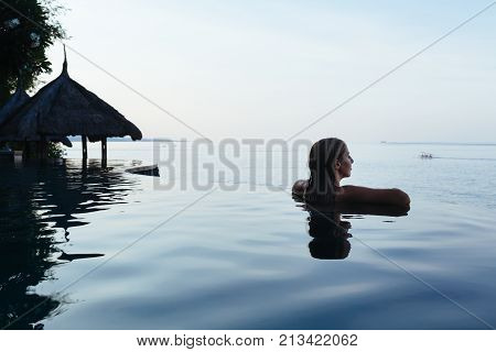 Black silhouette of happy woman on summer beach holiday relaxing in luxury spa hotel in infinity swimming pool with blue sea view. Healthy lifestyle family travel background. Tropical island tour.