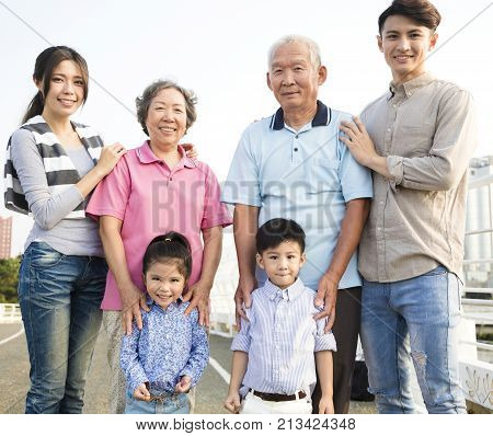 three generations asian family standing together outdoors