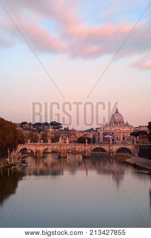 River Tiber in Rome with Vatican City St Peters Basilica and Ponte Sant Angelo after sunset