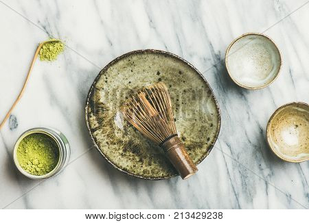 Flat-lay of Japanese tools and ceramic bowls for brewing matcha green tea. Matcha powder in tin can, Chashaku spoon, Chasen bamboo whisk, Chawan bowl, cups for ceremony, grey background, top view