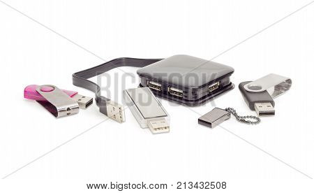 External separate USB hub in black square plastic casing with short cable and several different usb flash drives on a white background