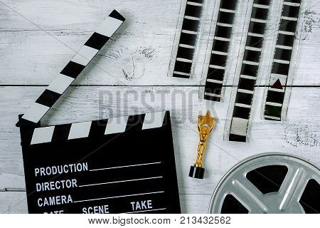 Clapperboard a reel with a film a striped film and a golden statuette lie on a table